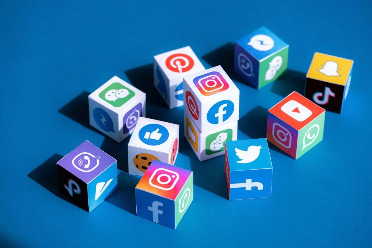 Würfel mit Social Media-Logos auf blauem Hintergrund.
